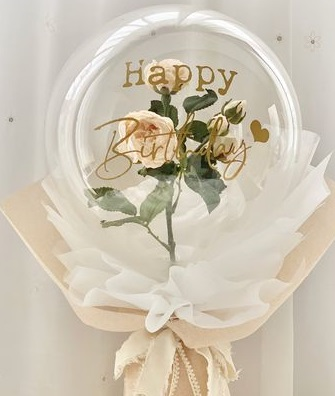 A bouquet of single clear balloon with happy birthday printed wrapped in white and jute