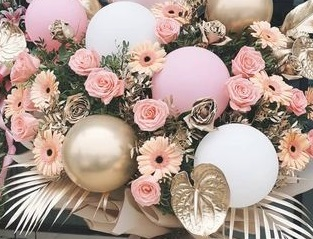 6 Pink Gold and White balloons  placed in between gold leaves and 20 pink roses and gerberas