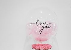 1 Printed Love You transparent Balloon with 3 pink balloons and pink petals inside and tied to 15 pink roses basket